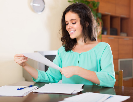 calculated: Happy brunette young woman reading document at home