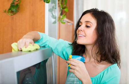 televisor: Smiling brunette woman cleaning TV with rag at home Stock Photo