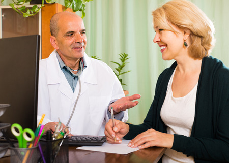 female doctor: Smiling male doctor talking with elderly female patient at the table Stock Photo