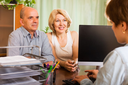 Positive senior female opening saving account in bank Stock Photo