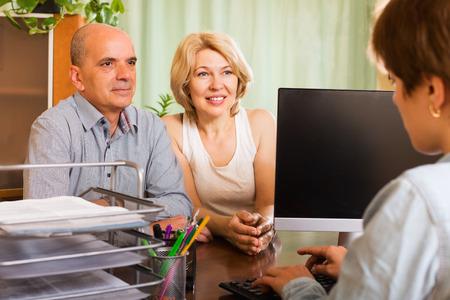 devise: Positive senior female opening saving account in bank Stock Photo