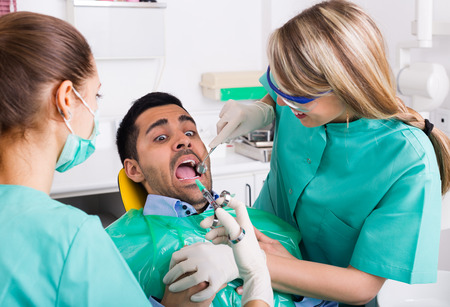 dismay: Portrait of doctor and frightened afraid patient at dental clinic