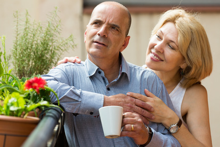Positive aged couple staying on balcony with tea cups in hands photo
