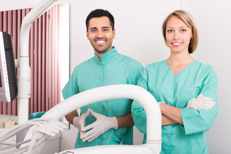 trained nurse: Happy dentist and head nurse standing at room and smiling Stock Photo