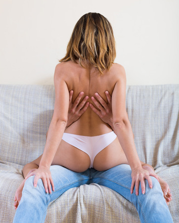 having sex: Sexy topless blonde woman and man having sex on sofa at home