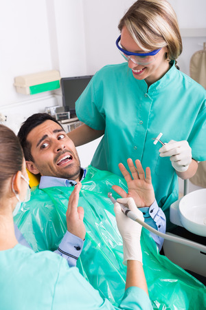 dental fear: Dentist with assistant and scared male patient at surgery office
