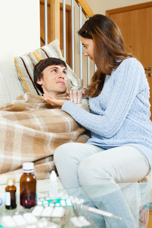 Girl giving  medicament to unwell husband at home. Focus on man