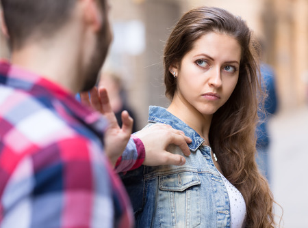 Couple on a conflict. Man is chasing his girlfriend on a street but she doesnt want to talk to him Stock Photo