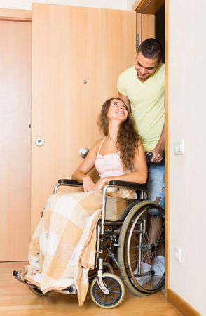 invalidity: Happy couple with girl in wheelchair near apartment entrance