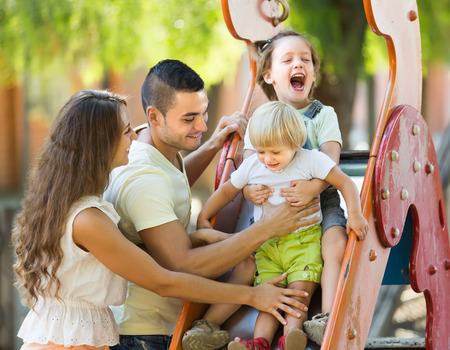 子供のスライドで遊ぶ 2 人の娘と幸せな親は。男に焦点を当てる