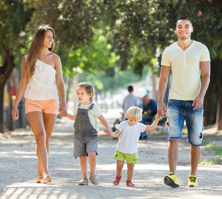family of five: Young parents with little children in park on summer day