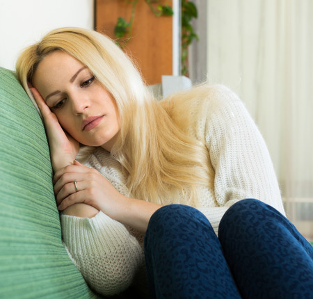 heartbreak issues: Portrait of upset young woman suffering from troubles in home Stock Photo