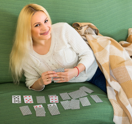 predictor: Beautiful young woman luying on a couch covered with a cozy blanket playing game of cards Stock Photo