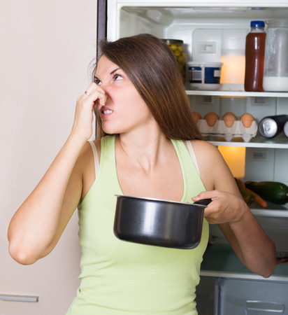 frowy: Young woman holding foul food near refrigerator in house