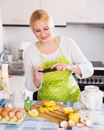 Woman with apples, eggs and phone doing selfie at kitchen
