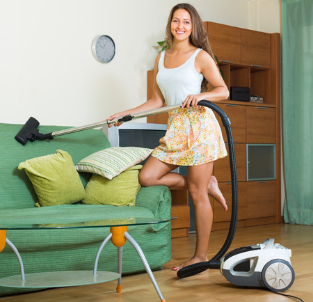 Mujer sonriente en falda limpieza salón con aspiradora