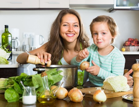 home cooking: Smiling young housewife with little daughter cooking at home kitchen Stock Photo