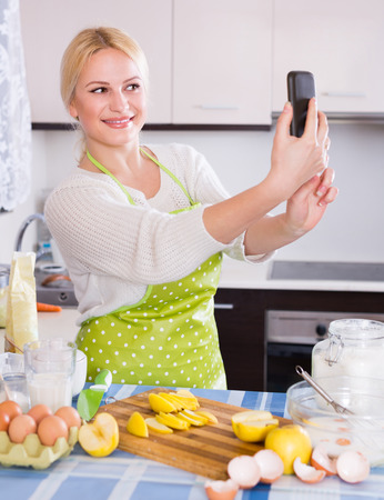 Girl in apron making selfie on smartphone at kitchen photo