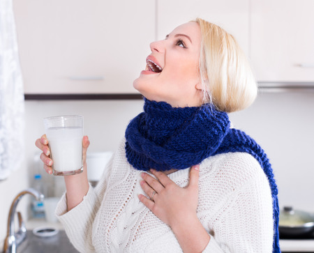 casual clothes: Blonde young woman having pain in throat and doing oral rinsing at kitchen Stock Photo