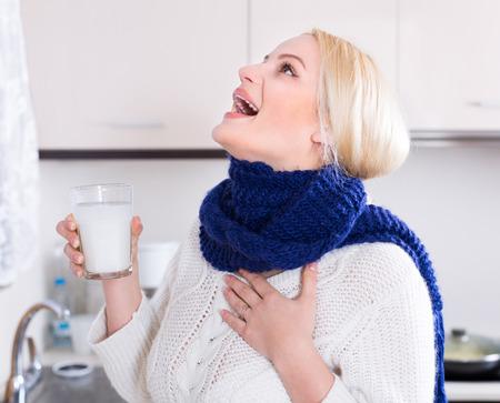 ropa casual: Mujer joven rubia que tiene dolor en la garganta y hacer un enjuague bucal en la cocina