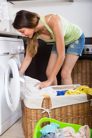 stereotypical: Young long-haired woman loading clothes in washing machine