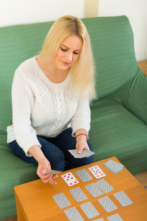Young smiling blonde girl playing solitaire at domestic interior