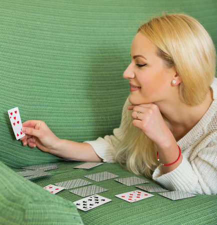 predictor: Relaxed young housewife on couch telling fortunes by cards indoors