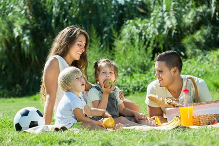 夏の日の公園でピクニックとの休日を持つ小さな娘と若い陽気な家族 写真素材