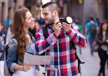 memorable: Tourists on a sightseeing tour in an old european town. Looking at a map and taking memorable photographs