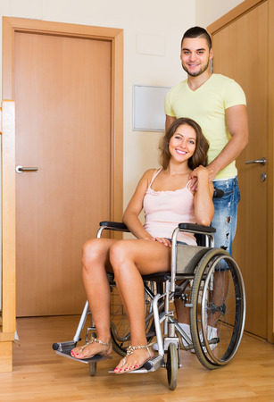 coming home: Young man and his positive disabled wife in wheelchair coming home. Focus on woman