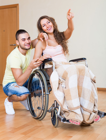 invalidity: Happy friends with smiling woman on wheelchair in playful mood