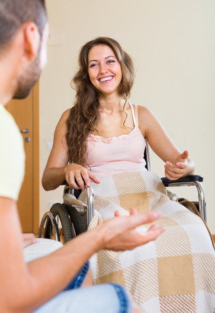 invalidity: Handsome man and his handicapped russian girlfriend in wheelchair having conversation