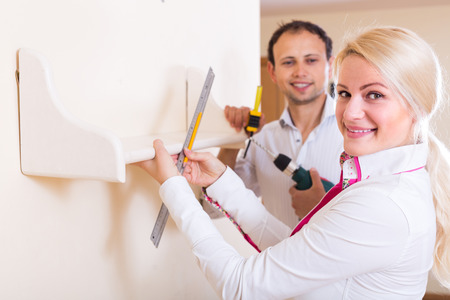 repairs: Positive smiling young family makes repairs together at home Stock Photo