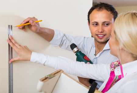 white work: Young married couple makes repairs at home and smiling Stock Photo