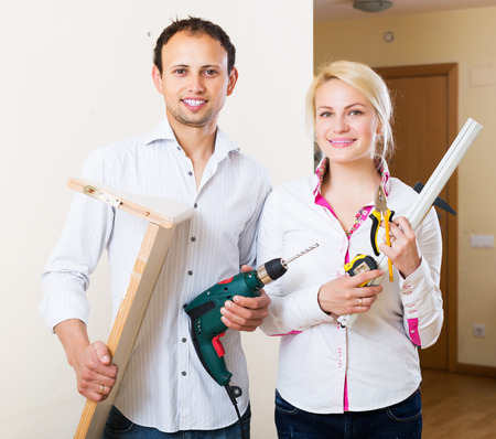 modifying: Happy young man and woman choosing place for shelf at home Stock Photo