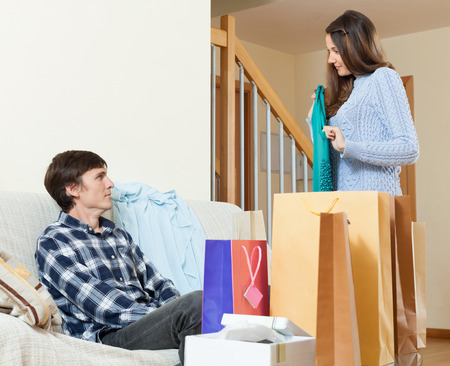 disgruntled: Woman showing purchases  to disgruntled boyfriend at  home
