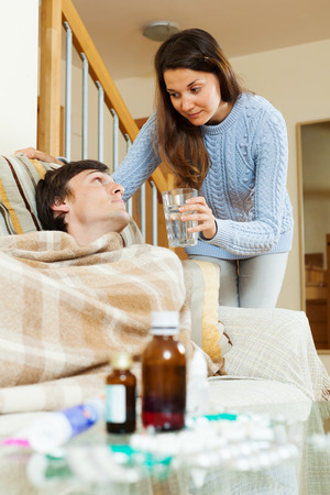 caring for: Girl caring for sick husband in  room Stock Photo