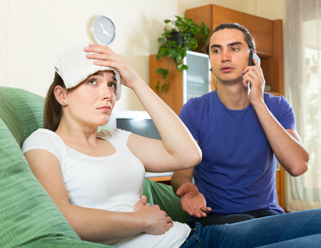 accession: Man calls an ambulance for his sick woman at sofa Stock Photo
