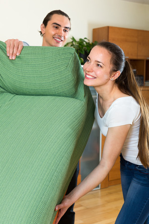 Man and woman moving furniture in room Stock Photo