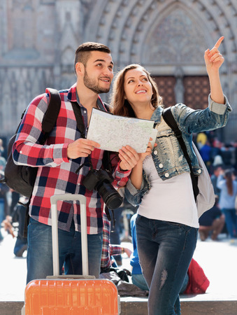 Portrait cheerful couple of travellers with map at street photo