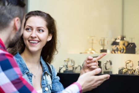shopwindow: Smiling couple of tourists choosing wristwatch at shopwindow
