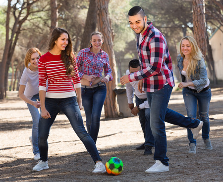 Positive adult friends playing football at picnic lunch. Selective focus photo