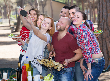 mutual: Positive young colleagues making mutual photo at summer grill party Stock Photo