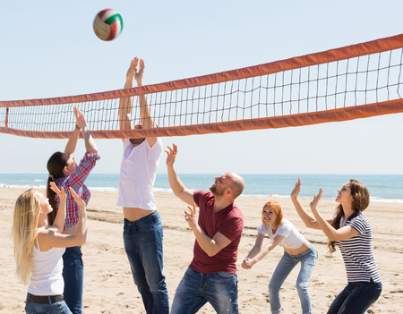 Heated active adult friends playing volleyball at sandy beach photo