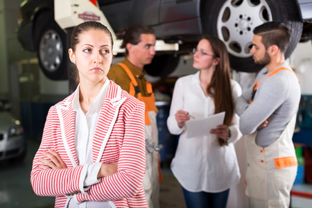 unsatisfied: Client at a car dealership is unsatisfied with the result of repairs mechanics done to her car Stock Photo
