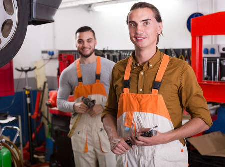 toiling: Two happy workmen toiling at a locksmiths workshop and smiling Stock Photo