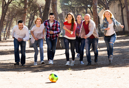 freetime activity: Positive adults chasing ball outdoors at sunny day