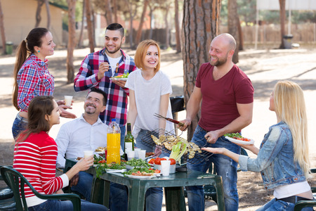 adult: Smiling adults friends relaxing at grill party in sunny day