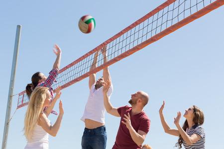voleibol: Amigos activos calefactables jugando voleibol en la playa de arena