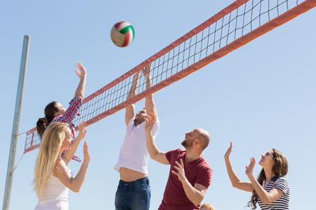 Heated active friends playing volleyball at sandy beach Stock Photo